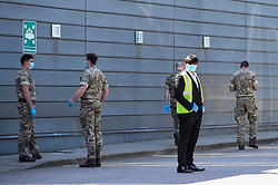 © Licensed to London News Pictures. 26/04/2020. WATFORD, UK. A security staff member and members of the military at a pop-up mobile coronavirus testing centre at Watford Leisure Centre Central.  The testing centre manned by the military is open only for NHS staff and other key essential workers, and is one of mobile testing centres set up by the government to accelerate the testing programme to move towards a target of 100,000 tests per day by 30 April set by Matt Hancock, Health Secretary.  Photo credit: Stephen Chung/LNP