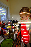Young girl with apron bakes a cake Model release Available