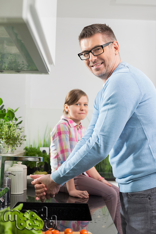 Portrait of smiling man washing hands with daughter sitting on counter in kitchen