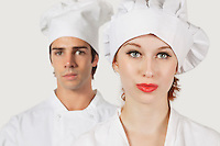 Portrait of young man and woman in chef's uniform against gray background