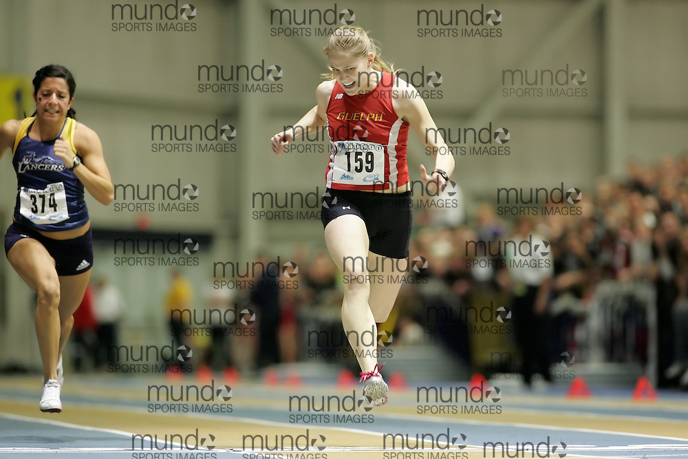 (Windsor, Ontario---11 March 2010) Sarah Peirce of University of Guelph Gryphons runs to second place in the 60m final with a time of 7.45s, ahead of Nicole Sassine of University of Windsor Lancers (374), who finished 6th with a time of 7.62 at the 2010 Canadian Interuniversity Sport Track and Field Championships at the St. Denis Center. Photograph copyright Sean Burges/Mundo Sport Images. www.mundosportimages.com
