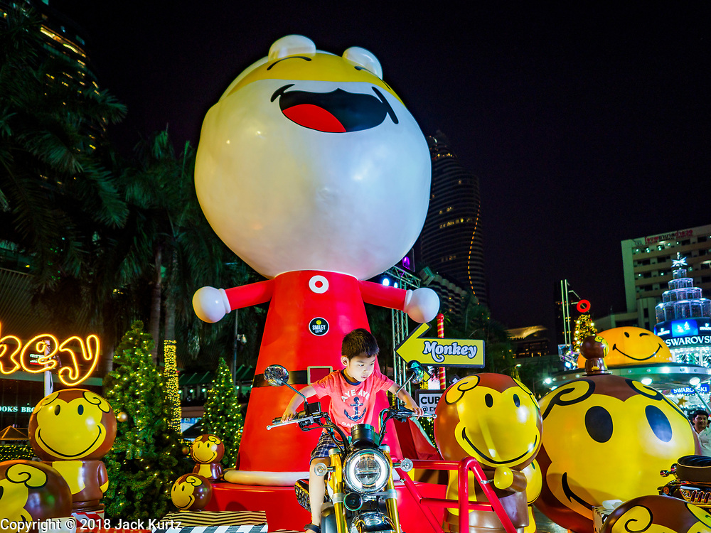 """23 NOVEMBER 2018 - BANGKOK, THAILAND: A child sits on a motorcycle in the """"World of Happiness,"""" the Christmas display at Central World, a large mall in Bangkok. Although Thailand is an overwhelmingly Buddhist country, the commercial aspects of Christmas are widely observed, especially in Thailand's urban areas, which have large concentrations of Europeans and Americans.   PHOTO BY JACK KURTZ"""
