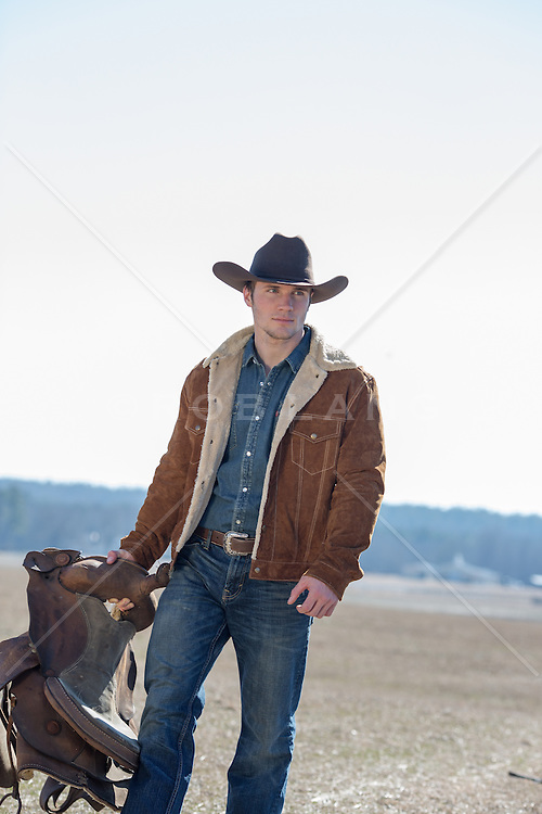 hot cowboy walking with a saddle in his hand on a ranch