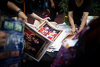 BANGKOK, THAILAND - October 26, 2017: Large photographs of the kings are handed out to crowds near the Grand Palace in Bangkok, Thailand. Hundreds of thousands of people, dressed in black, have gathered in Bangkok over a year after the death of Thailand's popular King Bhumibol Adulyadej.  The five-day royal cremation ceremony is taking place between October 25-29 in Bangkok's historic Grand Palace and the Sanam Luang area.