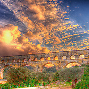 An epic cloud break at sunset over the ancient roman aqueduct - the Pont du Gard.