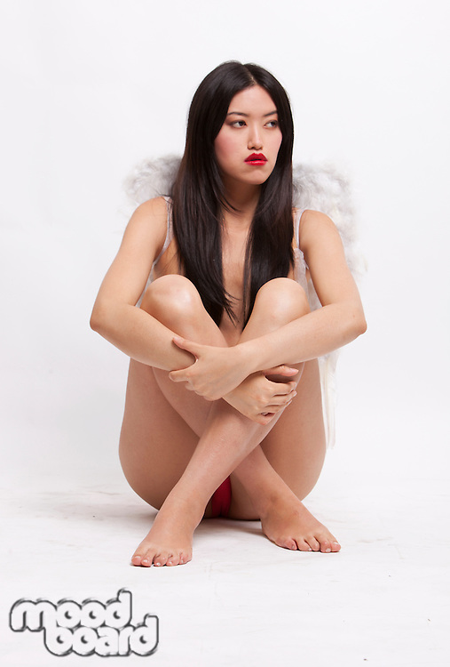 Young woman with angel wings sitting on floor against white background