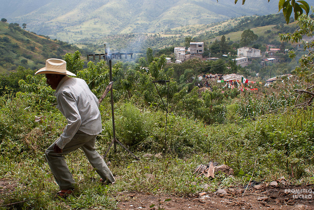 An old man manipulates fireworks in a hill next to the Tlatlatzohuaya (Cerro de la Cruz). The man runs after lighting a small fuse. (Photo: Prometeo Lucero)