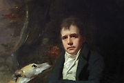 Portrait of Walter Scott with his dogs Camp and Percy in the Yarrow valley, detail, painted 1809 by Sir Henry Raeburn, 1756-1823, in the Chinese drawing room, in Abbotsford House, built 1817-25 by Sir Walter Scott, 1771-1832, Scottish writer and poet, near Melrose, in the Borders, Scotland. The building is in Scottish Baronial style and includes Scott's personal collections of books, furniture and Scottish historical artefacts, making it a centre for European Romanticism. The Scott family still own the building, which is open to the public as a tourist attraction. Picture by Manuel Cohen