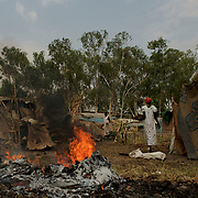 Local women pass by burning rubbish outside some shacks in central Juba, South Sudan.