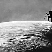 Mark Kogelmann clicks into his bindings getting ready to drop a wind lip in the backcountry near Mt Baker Ski Area.