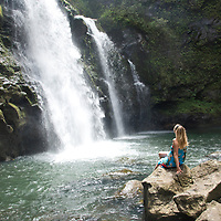 Woman relaxing at a triple waterfall (Three Bears Falls) along the famed Road to Hana on Maui, Hawaii. Model released.