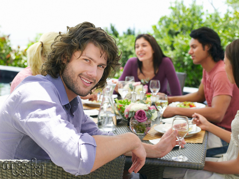 Young man enjoying outdoor dinner party smiling to camera