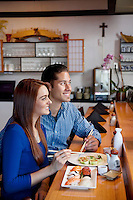 Happy young couple sitting at counter with sushi while looking away in restaurant