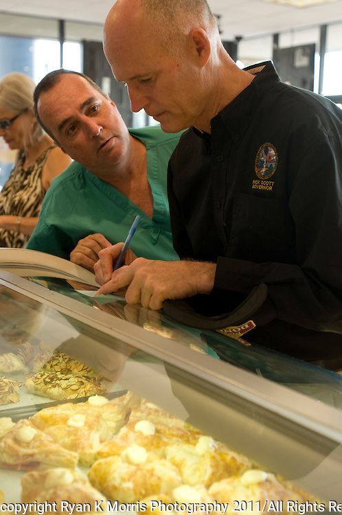 """Florida Governor Rick Scott served doughnuts  to customers at NicolaÕs Donuts and Bakery in Tampa, FL as part of his """"workday"""" initiative on Wednesday, August 3, 2011. The """"workdays""""  mirror efforts of former Gov. and U.S. Sen. Bob Graham Bob Graham and are intended to allow the governor to spend time doing jobs with regular Floridians. .Photos by Ryan K. Morris"""