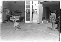 Little girl dancing alone in garage, South-East London, London street photography in 1982. Tri-X