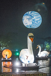 © Licensed to London News Pictures . 19/07/2013 . Suffolk , UK . A woman suspended from a moon balloon and giant swan sculptures with ballet dancers performing as Studio Festi perform Water Dance above a lake in Henham Park after sunset on the opening night of The Latitude music and culture festival in Henham Park , Southwold . Photo credit : Joel Goodman/LNP