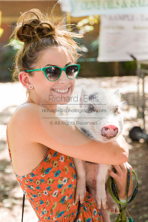 A young woman holds her Juliana teacup pet pig at a farmers market in Wicker Park August 2, 2015 in Chicago, Illinois, USA