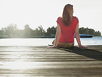 Woman sitting on edge of jetty back view