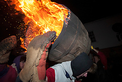 © Licensed to London News Pictures. 05/11/2014. Ottery St Mary, Devon, UK.  The custom of barrel burning, carrying flaming tar barrels through the crowds and streets of the town on bonfire night, 05 November.  Picture of the intermediates' barrel burning. Photo credit : Simon Chapman/LNP