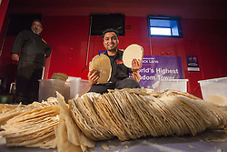 © licensed to London News Pictures. London, UK 20/07/2012. Raymam Miah, a cook from Poppadom Restaurant posing with poppadoms after the world's highest poppadom tower record fails in Brady Arts and Community Centre. The 161cm tall tower managed to stand only 8 seconds but rules require 10 second to break the official world record. The record attempt was the part of the Curry Capital Festival in Brick Lane. Photo credit: Tolga Akmen/LNP