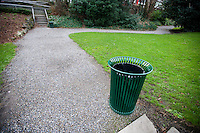 Wide angle view of trash can by a path in a park