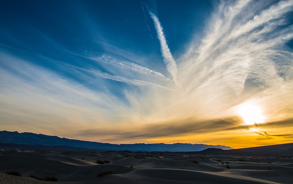 The sky above Death Valley Desert is painted with the first rays of light, a cloud formation, and few jet contrails.
