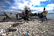 080923-N-9620B-003 - GONAIVES, Haiti (September 23, 2009) - Haitian relief workers assist U.S. military service members embarked aboard USS Kearsarge (LHD 3) unload food and water to aid those affected by the recent hurricanes. Kearsarge embarked personnel from the Navy, Army, Air Force, Marines, and Coast Guard, along with medical personnel from the U.S. Public Health Service, Canadian Army, Air Force and Navy, Brazil, Project Hope and International Aid are working together to conduct hurricane relief operations in Haiti.   (U.S. Navy photo by Mass Communication Specialist  2nd Class Erik C. Barker/Released)