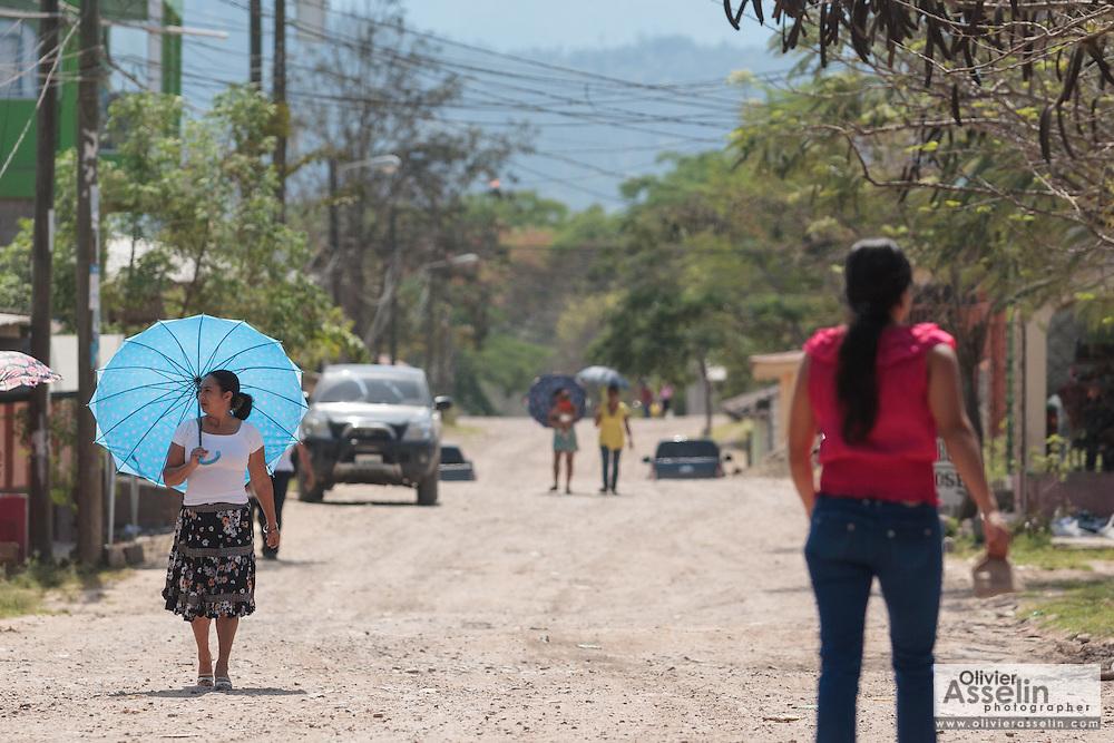 A woman carrying a blue umbrella walks down a street in the town of San Esteban, Honduras on Wednesday April 24, 2013.