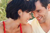 Happy Couple sitting face to face in grass close up portrait