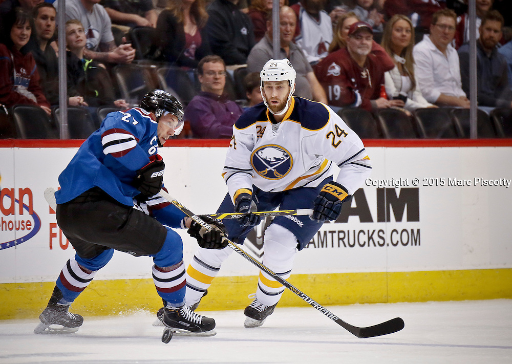 SHOT 3/28/15 7:11:32 PM - The Colorado Avalanche's Jordan Caron #27 loses the puck in front of the Buffalo Sabres' Tyson Strachan #24 during their regular season NHL game at the Pepsi Center in Denver, Co. The Avalanche won the game 5-3. (Photo by Marc Piscotty / © 2015)