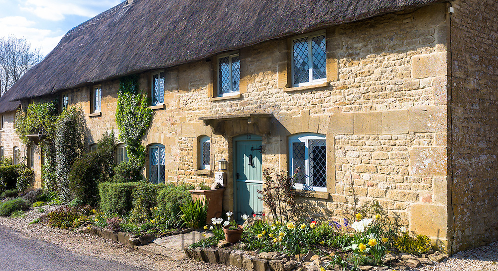Quaint thatched cottage with traditional thatching and leaded light windows at Taynton in The Cotswolds, Oxfordshire, UK