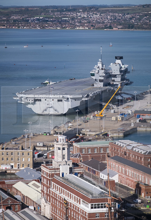 © Licensed to London News Pictures. 25/10/2017. Portsmouth, UK.  A view of HMS Queen Elizabeth alongside in Her Majesty's Naval Base Portsmouth.<br /> <br /> The departure of the Royal Navy's flagship, HMS Queen Elizabeth, from HMNB Portsmouth has been delayed for the second day in a row. The aircraft carrier has been alongside in Portsmouth since 16th August 2017, and was due to sail on Monday 23rd October for the second stages of her sea trials. Her departure was originally delayed due to strong winds, and is now expected to be delayed until Friday at the earliest.<br /> <br /> Flight trials involving the new F-35B Joint Strike Fighter are expected to take place off the coast of the U.S. next year, and she is due to come into service in the early 2020s.  Photo credit: Rob Arnold/LNP