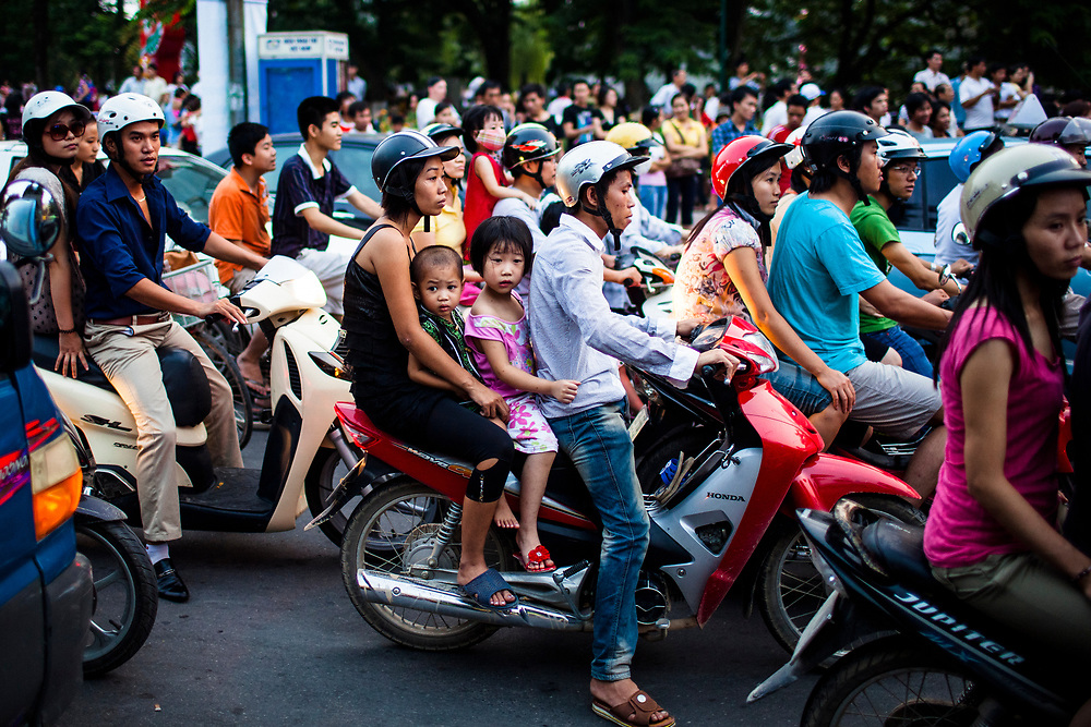 A family waits piled on their motorbike in the crowded, congested streets of Hanoi, Vietnam, during rush hour on a  public holiday.