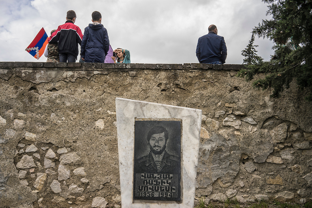 A family poses for a picture near the grave of a fighter killed in the 1990s war between Armenia and Azerbaijan following a ceremony commemorating both the victory over Nazi Germany in the Second World War as well as the fall of the strategic town of Shushi to Armenian forces on Monday, May 9, 2016 in Stepanakert, Nagorno-Karabakh.