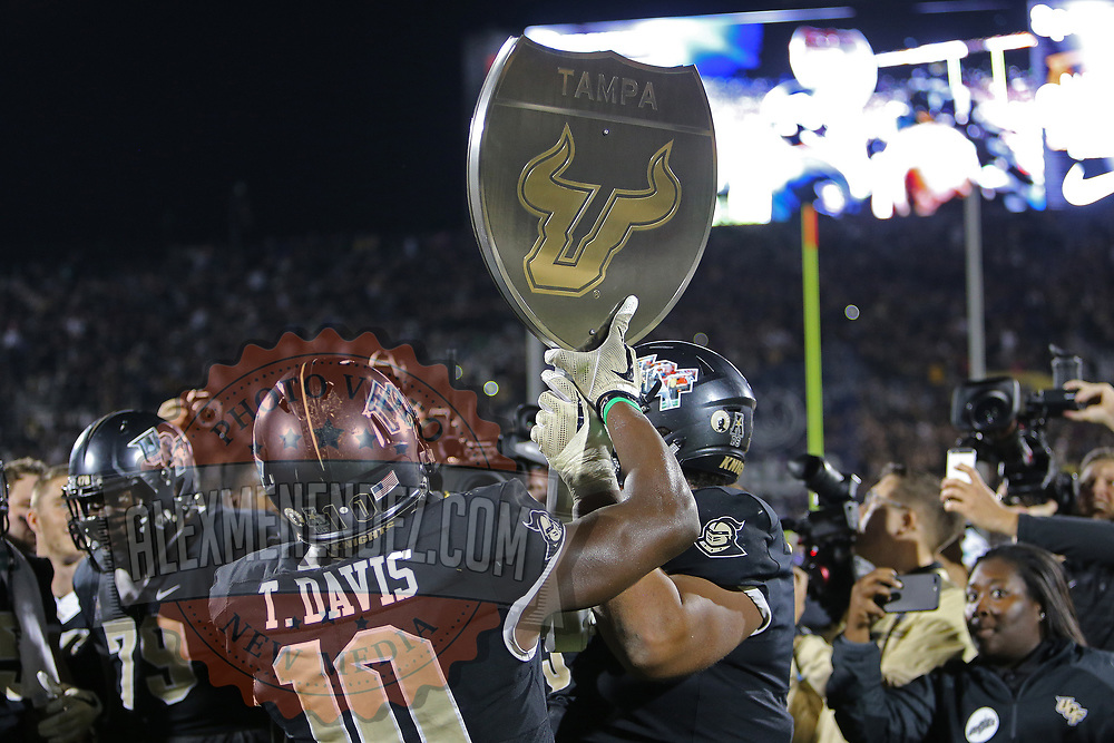 """UCF Knights linebacker Titus Davis (10) holds up the """"War on Interstate 4"""" street sign trophy during a NCAA football game between the University of South Florida Bulls and the UCF Knights at Spectrum Stadium on Friday, November 24, 2017 in Orlando, Florida. (Alex Menendez via AP)"""