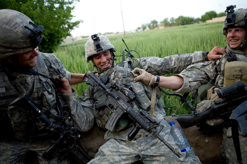 The 82nd Airborne's Sargeant Dustin Kerrins, left, and Specialist Jacob Allen, right, grab Specialist Adam Holmgren, center, before his packed filled with ammunition pulls him over a wall in Sangin, Helmand province, Afghanistan on Saturday, April 7, 2007.