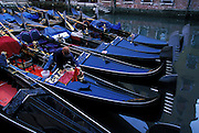 Gondolier cleans his boat as it rests in row of gondolas in canal, Venice, Italy..Subject photograph(s) are copyright Edward McCain. All rights are reserved except those specifically granted by Edward McCain in writing prior to publication...McCain Photography.211 S 4th Avenue.Tucson, AZ 85701-2103.(520) 623-1998.mobile: (520) 990-0999.fax: (520) 623-1190.http://www.mccainphoto.com.edward@mccainphoto.com.