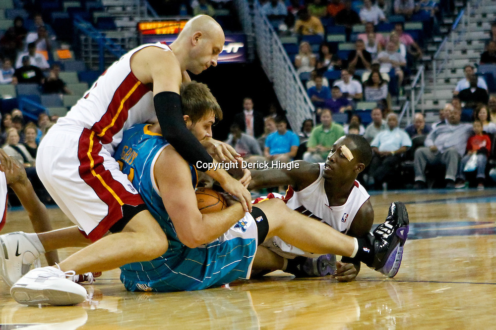 October 13, 2010; New Orleans, LA, USA; New Orleans Hornets center Aaron Gray (34) scrambles for a loose ball with Miami Heat center Zydrunas Ilgauskas (11) and point guard Patrick Beverley (12) during the second half of a preseason game at the New Orleans Arena. The Hornets defeated the Heat 90-76. Mandatory Credit: Derick E. Hingle
