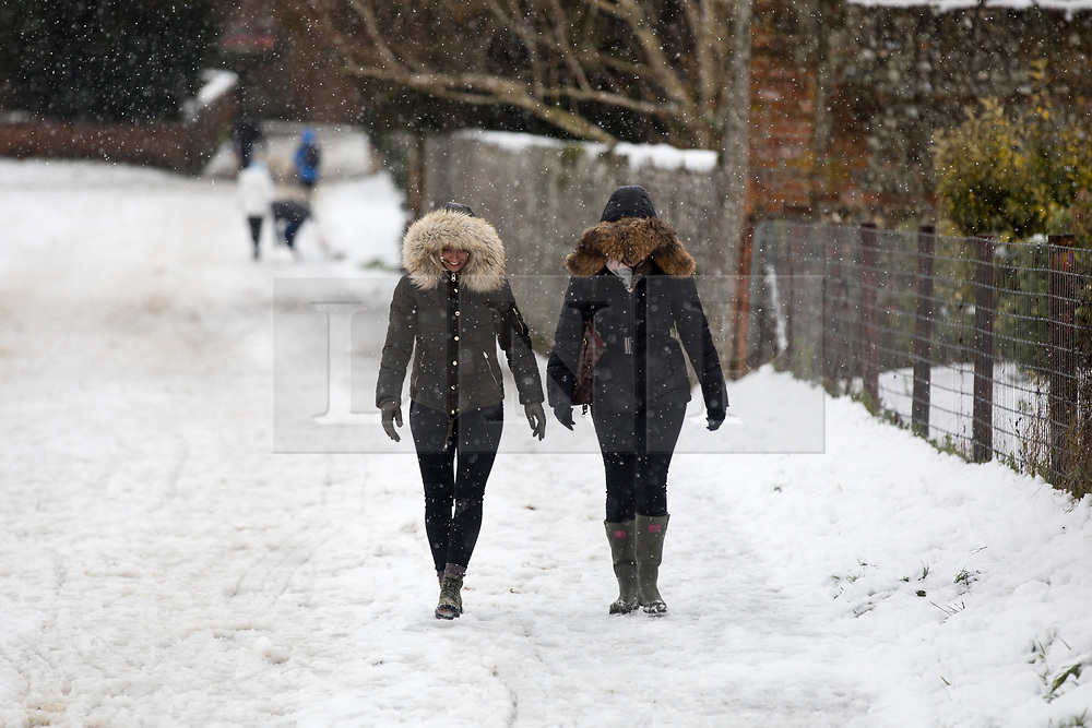 © Licensed to London News Pictures. 11/12/2017. Amersham, UK. Two women walk through the snow in Amersham. Yesterday parts of the south east of England experienced heavy snow, with the home counties experiencing some of the worst conditions. Many schools in the area are closed today. Photo credit : Tom Nicholson/LNP
