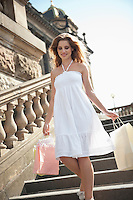 Happy young woman carrying shopping bags walking on staircase