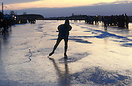Nederland, Friesland, 19970104..De Elfstedentocht in januari 1997 in Friesland..Schaatsers rijden door de polders.  Mensen staan te kijken naar de schaatsers die voorbij komen. 6000 schaatsers en meer dan een miljoen toeschouwers..De zon is al bijna onder. Lange schaduwen op het ijs...The Elfstedentocht is a speed skating competition and leisure skating tour in the province of Friesland in the Netherlands..6.000 skaters and over a million spectators were present. The route takes the skaters through eleven cities in Frisia, in the North of Holland. 200 kilometre race along the frozen canals of Friesland..The sun has almost set. Long shadows on the ice.