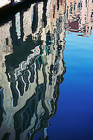 Reflection of buildings in water of canal Venice Italy