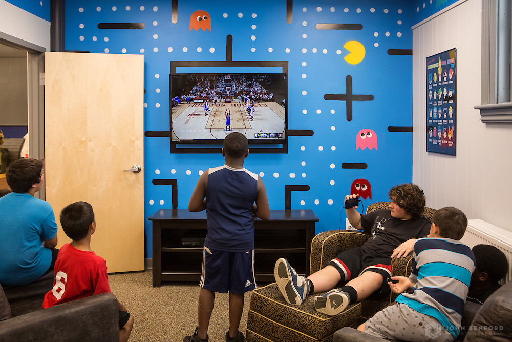 A group of boys plays video games in the newly renovated entertainment center at the reveal ceremony for the 2016 Building on Hope project at the Michael Briggs Community Center / Manchester Police Athletic League in Manchester, NH.