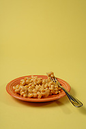 Side view of macaroni and cheese on an orange plate with fork with a yellow background.