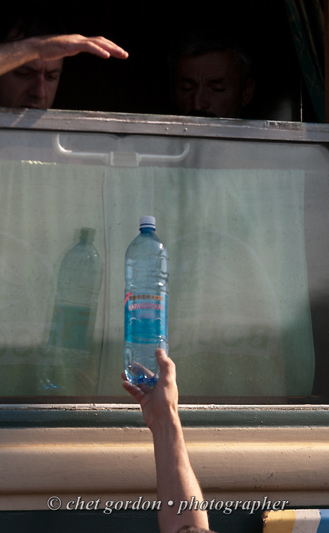 A passenger onboard a Trans-Siberian Railway wagon reaches for a bottled water in Marinsk, Russian Federation on June 13, 2005.