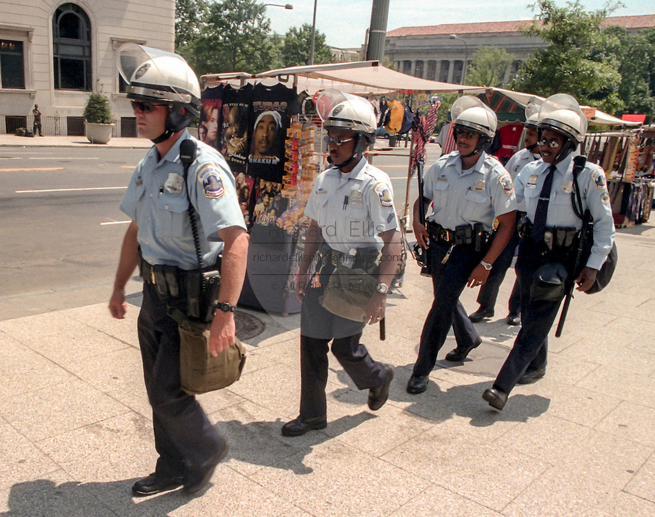 District of Columbia riot police walk toward James Monroe Park where a neo-Nazi group was scheduled to hold a demonstration August 7, 1999 in Washington, DC. The neo-Nazi group canceled a planned march past the White House after only four members showed up.