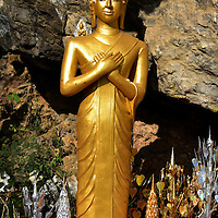 Contemplation Buddha on Mount Phousi in Luang Prabang, Laos  <br /> Each part of a Buddha statue has a meaning to the Lao people. This standing position or madrā with arms crossed over the chest is the Contemplation Buddha. It signifies determination, patience and understanding.  The monastic robe is shown in the open mode leaving the right shoulder exposed which demonstrates humility.  The spike or spire on his skull is called an usnīsa.  The long earlobes depicts when he was weighed down by earthly processions.