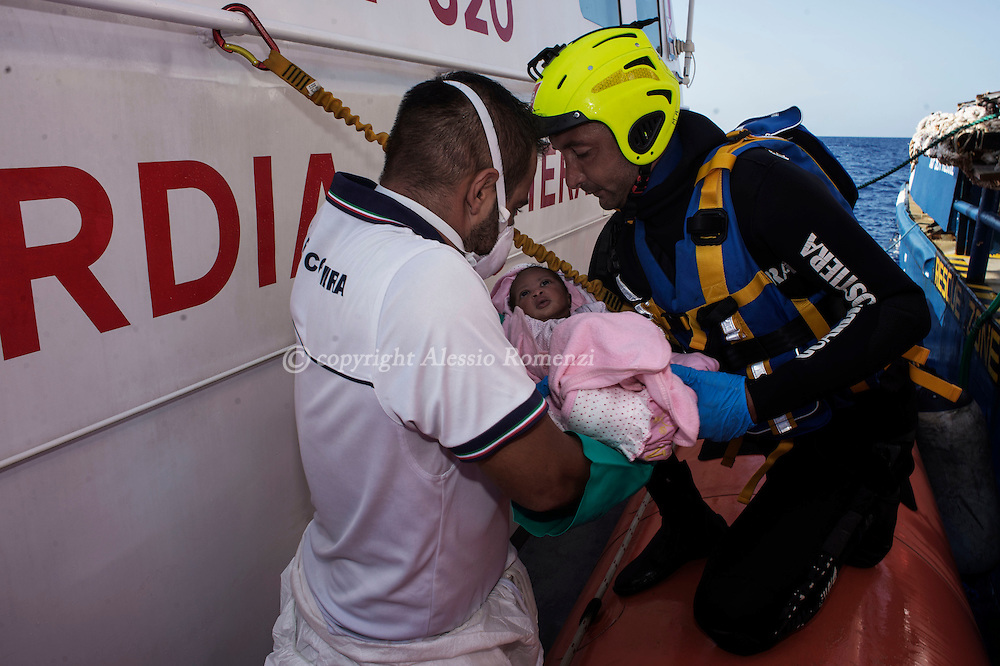 Italy: MSF Dignity1: Italian coast guard officials transfer an African migrant child rescued at sea on the Dignity1 on August 23, 2015. Alessio Romenzi