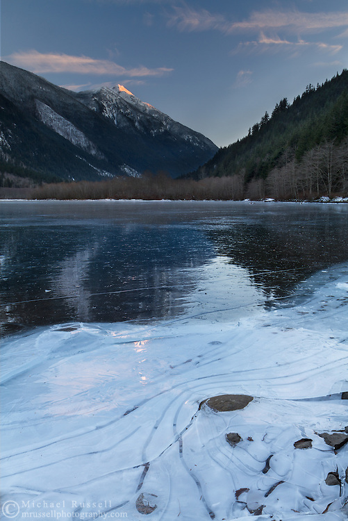 Ice patterns form in the ice along the shore of Silver Lake in Silver Lake Provincial Park near Hope, British Columbia, Canada. Mount Grant is in the background.