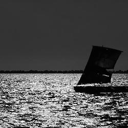 Pescador artesanal e com o seu barco a vela na baía do Mussulo. Angola
